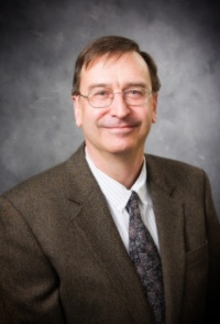 dr. weidlich wearing a brown suite and glasses