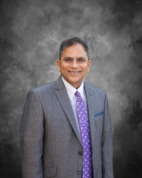 Dr. Shekar wearing a grey suit and purple tie smiling