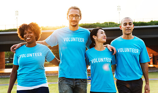 four volunteers standing arm in arm