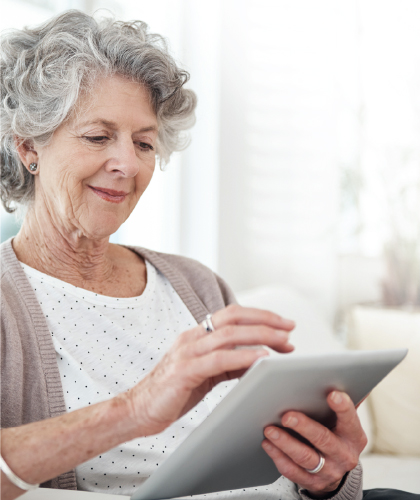 older woman reading on ipad