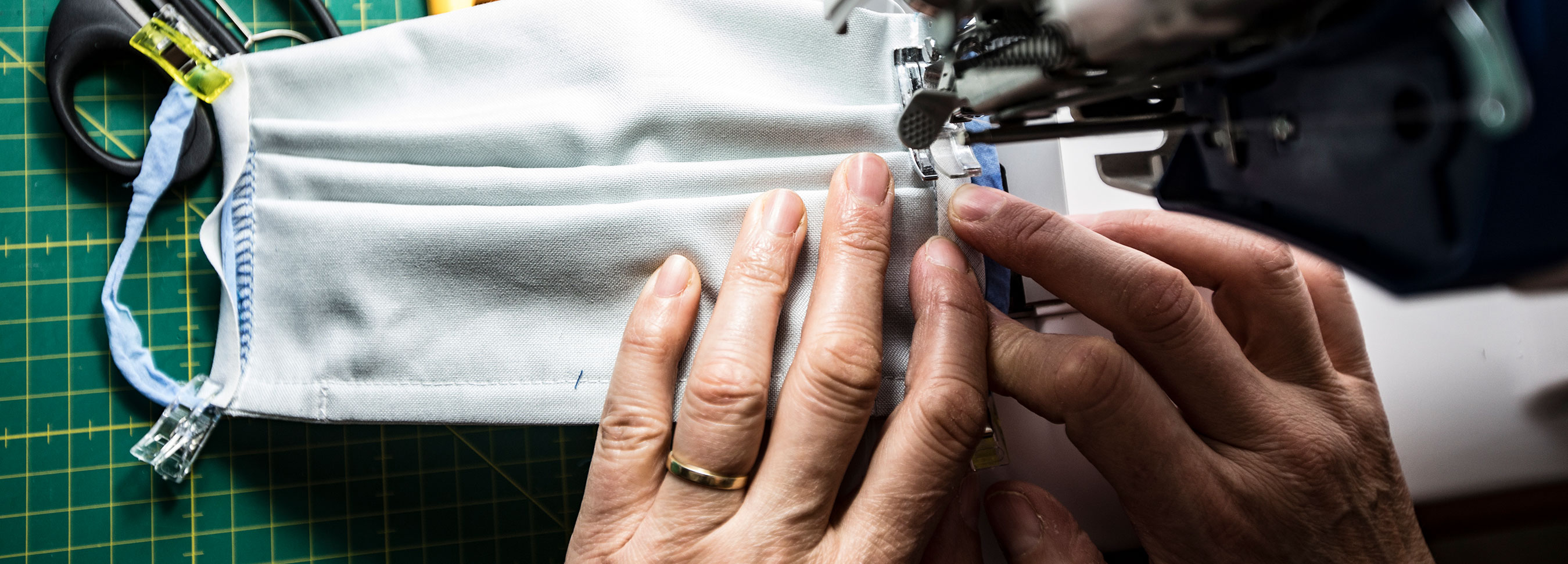 Image of woman sewing handmade face covering on sewing machine