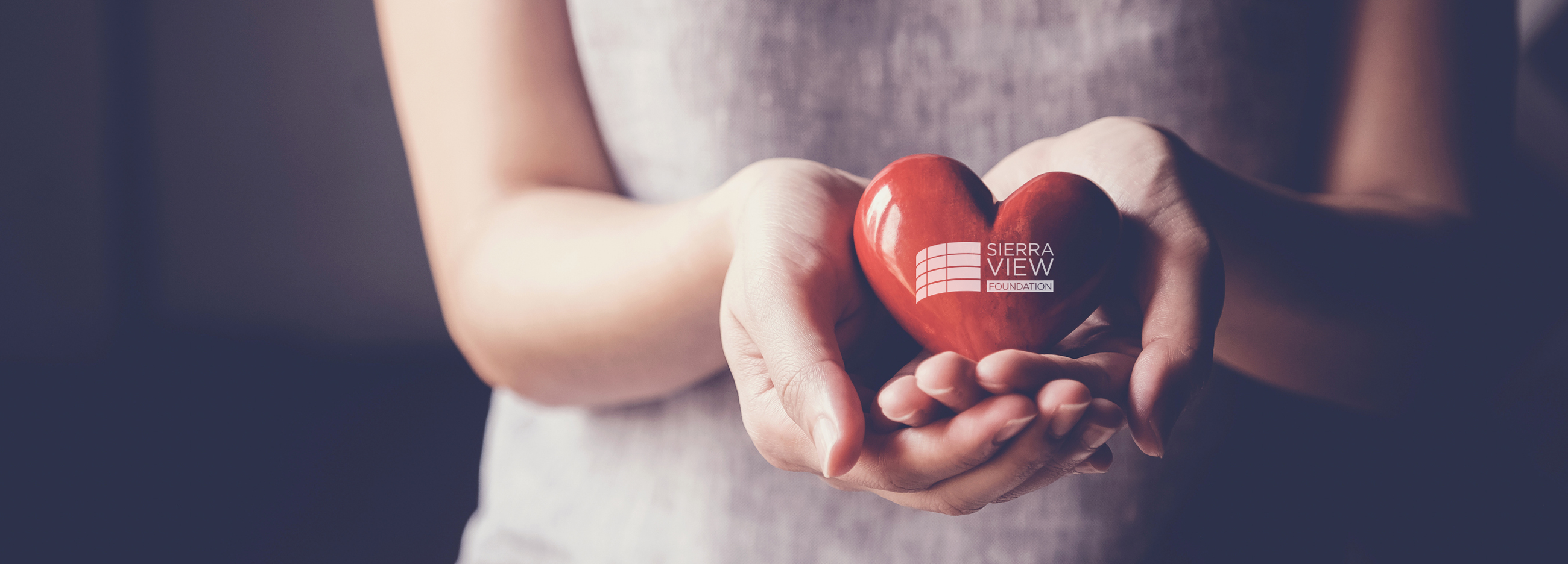 Image of woman holding ceramic heart in hands with Sierra View Foundation logo.